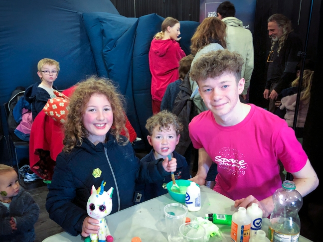 Children making glow-slime in front of the planetarium at Space@TheStade