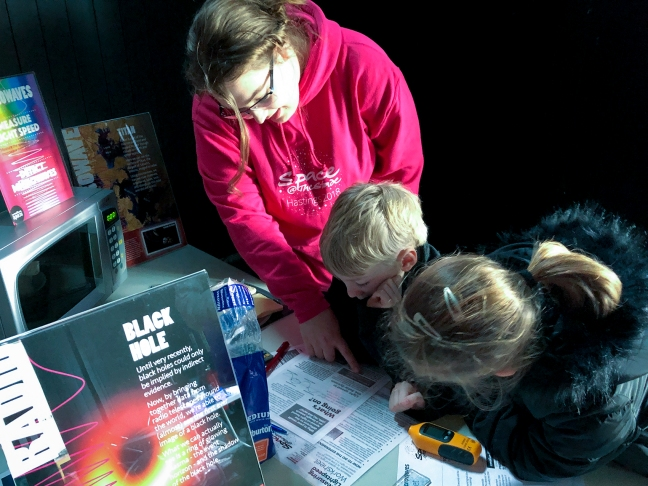 Creative Space volunteer explaining how to measure the speed of light in a microwave