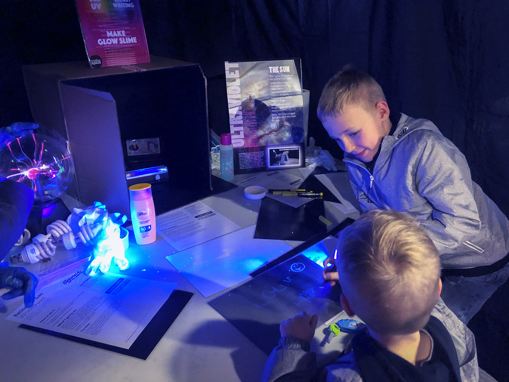 Children getting hands-on with the Secret Writing drop-in workshop at the Space@TheStade electromagnetic spectrum event