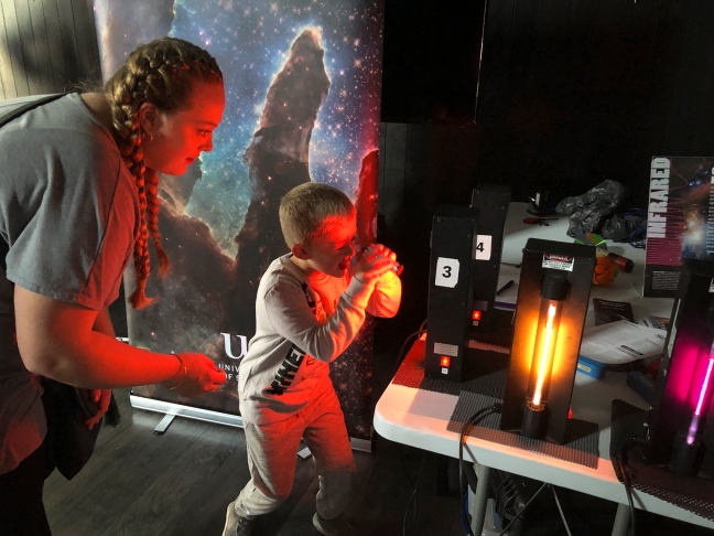 Child getting hands-on with a spectroscope and spectral tubes
